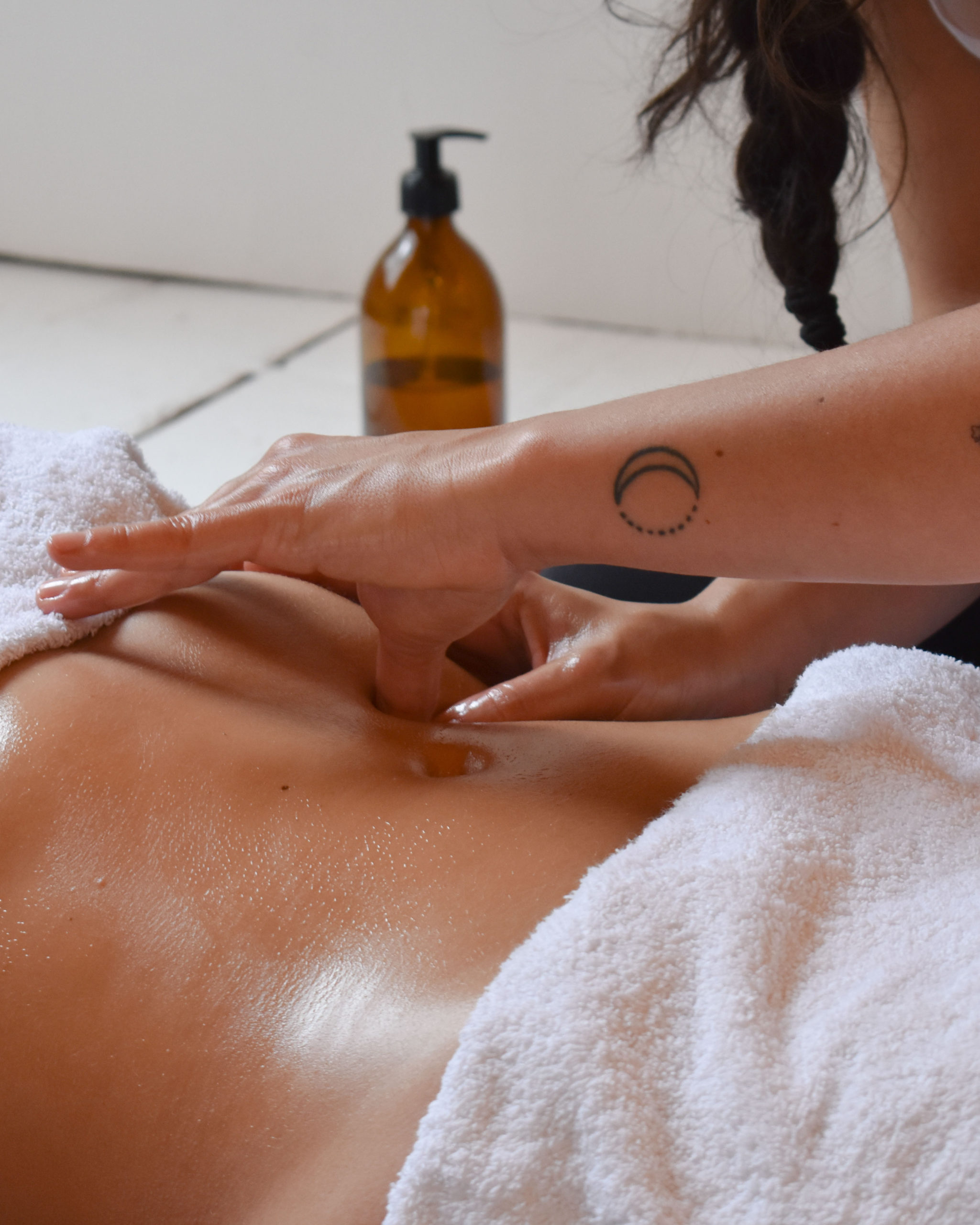 Chi Nei Tsang: holistic belly massage; you see the hands of Steffi massaging a belly with on the background massage oil.